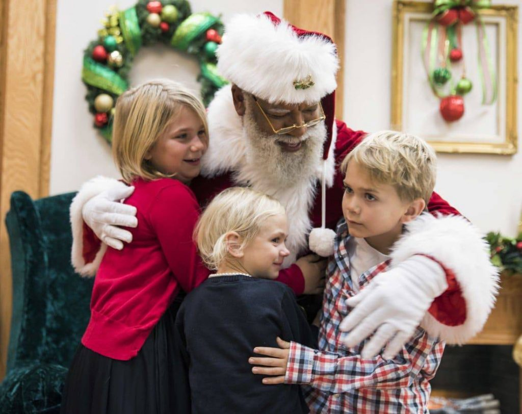 In this Thursday, Dec. 1, 2016 photo, Larry Jefferson, playing the role of Santa, gets a hug from Olivia Major, left, her sister Mallory and brother Preston, of Blaine, at the Santa Experience at Mall of America in Bloomington, Minn. The nation's largest mall is hosting its first-ever black Santa Claus this this weekend. (Leila Navidi/Star Tribune via AP)